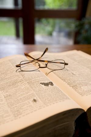 reference book: Un antiguo libro de referencia con las viejas p�ginas amarillas y un par de vasos en la parte superior.