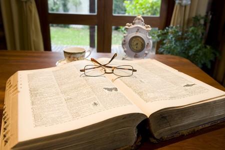 reference book: Un libro de referencia de antig�edades con anteojos y un reloj antiguo. Foto de archivo