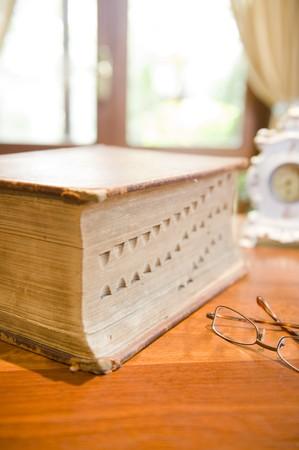 reference book: Un antiguo libro de referencia con gafas y un reloj antiguo.