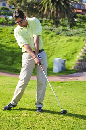 A golfer in action on a practice range, hitting the ball with a club. Stock Photo