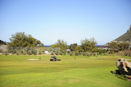 driving range: A beautifully maintained practice or driving range with distance markers for golfers to practice on. A motorized vehicle is in the process of picking up balls on the range.
