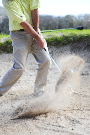A professional golfer playing a shot out of a sand-trap with excellent control.