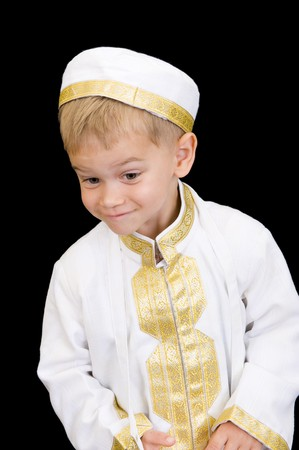 thobe: An adorable little boy dressed in Arabian thobe, isolated on black.
