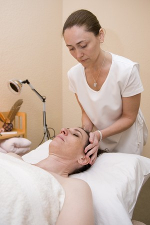 An attractive mature lady undergoing aromatherapy and massaging. photo