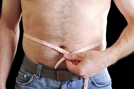 gain: Fit young man measuring his stomache with a white measuring tape. Stock Photo