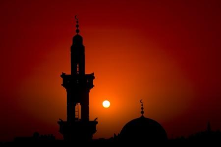 prayer tower: Il Silouette tipici di una moschea nei confronti di un rosso tramonto. Filtro rosso sulla lente per effetto aggiuntivo. Archivio Fotografico
