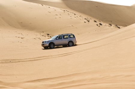 An offroad vehicle traversing some dunes in the desert. Stock Photo