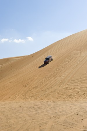 A 4x4 offroad vehicle driving down the steep slipface of a sand dune in the desert. photo