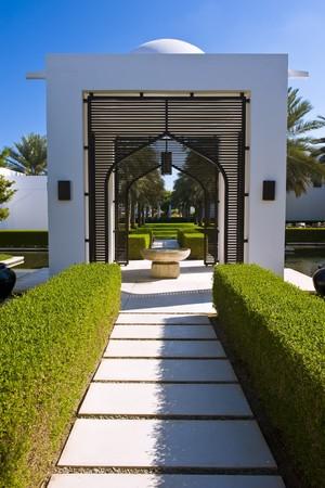 пышной листвой: Beautiful garden with lush foliage and small constructions.