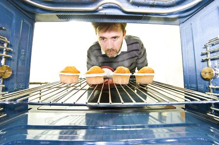A unique viewpoint from inside an oven while a man removes some freshly baked cupcakes. Stock Photo