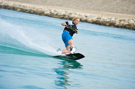 A wakeboarder enjoying the action of riding the wake of the boat. Stock Photo