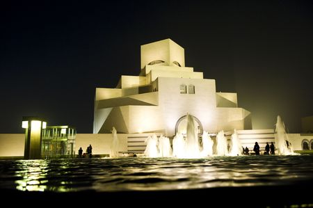 The ultra-modern Museum of Islamic Art in Doha, Qatar, across a fountain at night-time. Stock Photo