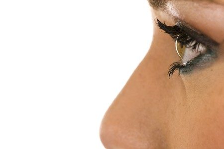 eye liner: Close-up profile of a young ladys eye with false eyelashes and makeup.