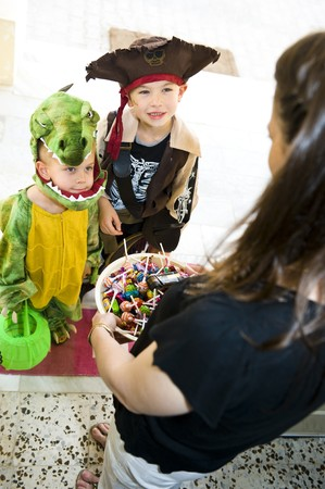 Kids in Halloween costumes playing trick or treat and asking for sweets. Stock Photo