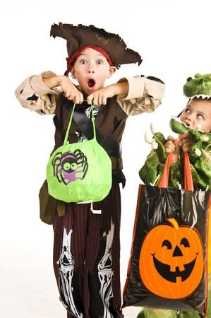 treat: Kids in Halloween costumes playing trick or treat and asking for sweets. Stock Photo
