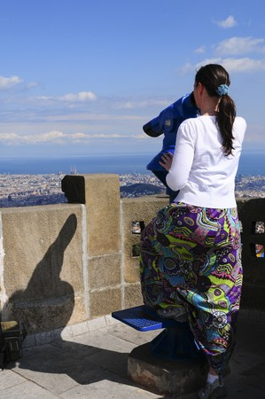 Woman looking at the city of Barcelona from Tibidabo, using a coin operated pair of binoculars. photo