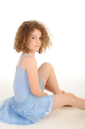 A gorgeous little girl with curly hair and ballet costume in the studio, white background. photo