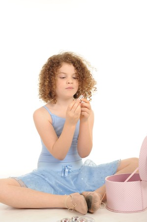 A gorgeous little girl with curly hair in the studio, wearing a ballet outfit and playing with make up, white background. photo