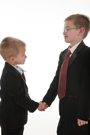 be dressed in: Two little boys dressed up in suits pretending to be businessmen and shaking hands. Isolated on white.