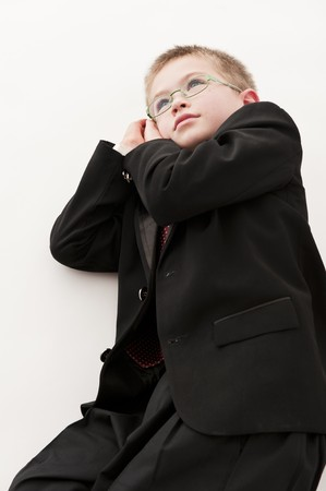 be dressed in: A small boy in the studio, dressed up in a suit and pretending to be a businessman, having a rest. Stock Photo