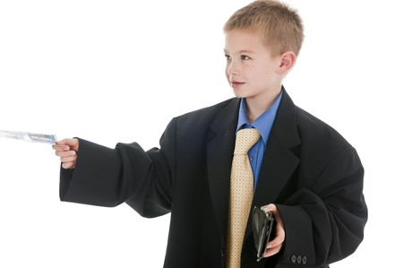 be dressed in: A small boy in the studio, dressed up in his fathers suit and pretending to be a businessman, handing money to someone. Isolated on white.