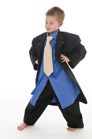be dressed in: A small boy in the studio, dressed up in his fathers suit and pretending to be a businessman. Isolated on white. Stock Photo