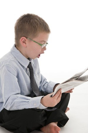 A small boy in the studio, dressed up in a suit and pretending to be a businessman, reading the newspaper. Isolated on white. photo