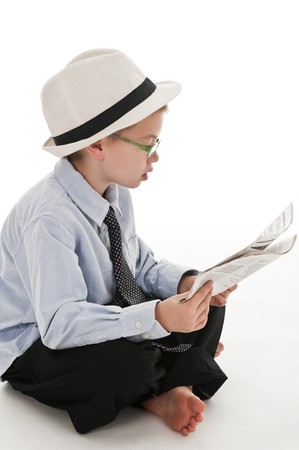 be dressed in: A small boy in the studio, dressed up in a suit and pretending to be a businessman, reading the newspaper. Isolated on white. Stock Photo