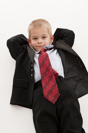 be dressed in: A small boy in the studio, dressed up in a suit and pretending to be a businessman, having a rest. White background. Stock Photo