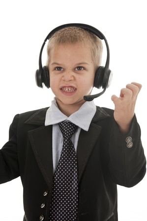 be dressed in: A small boy in the studio, dressed up in a suit and pretending to be a businessman, talking on a headset. Isolated on white.
