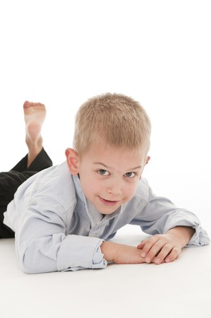 be dressed in: A small boy in the studio, dressed up in a suit and pretending to be a businessman, lying down. Stock Photo
