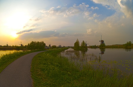 HDR image of windmills in the evening sunset after the rain, with the pedestrian or cycling path running through the middle. Stock Photo - 9535345