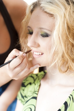 A beautiful young girl having makeup applied by a professional artist. photo