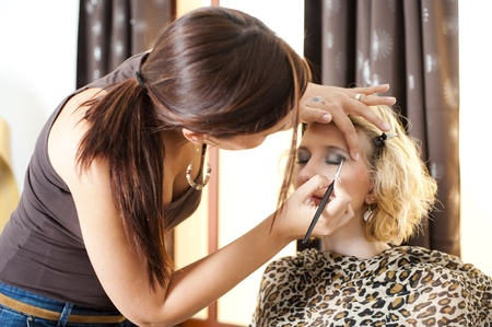 A beautiful young girl having makeup applied by a professional artist.