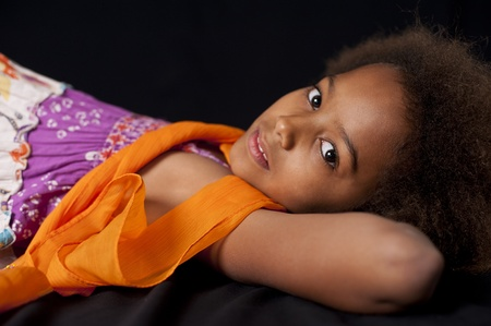 A gorgeous little 7yr old African girl in the studio. Black background.