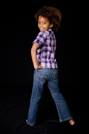 Eine wunderschöne 7 yr alt afrikanischen Mädchen im Studio. Schwarzer Hintergrund.