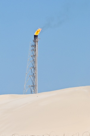 A candle burning off access gas at an oil refinery in the desert. photo