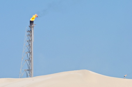 A candle burning off access gas at an oil refinery in the desert.