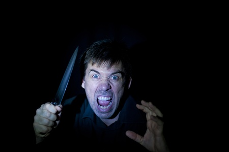 A crazy person with angry expression wielding a knife, on a black background. photo