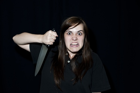 ugly mouth: A crazy person with angry expression wielding a knife, on a black background. Stock Photo