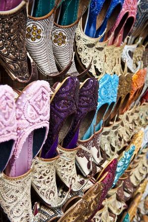 bur dubai: Rows of colorful shoes at the market in Dubai.