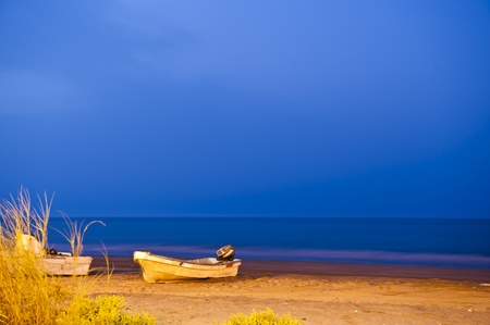muscat: 30 seconds shutter - evening shot of a fishing boat on a beach in the Seeb area in Oman, just after sunset.
