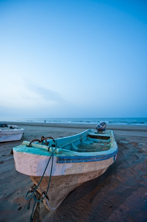 beached: Slow shutter fishing boat in the evening on a beach in Oman Stock Photo