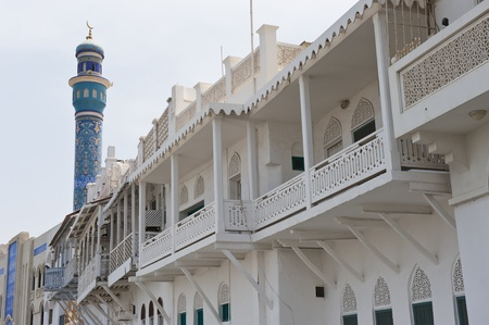 muttrah: Some traditional wooden balconies on buildings next to the Muttrah souq in Muscat Oman. A Shia muslim mosque minaret is visible to the left.