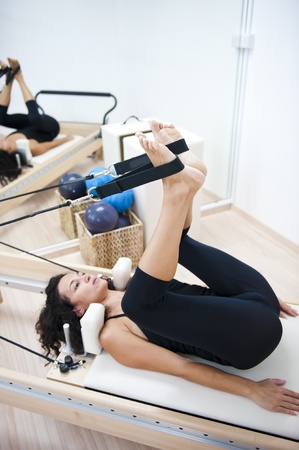 An attractive young lady performing a Pilates exercise with resistance from equipment. photo