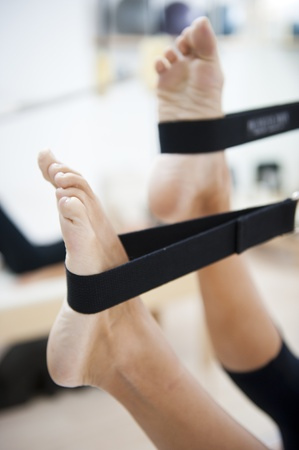 An attractive young lady performing a Pilates exercise with resistance from equipment.  Shallow DOF with focus on the feet.