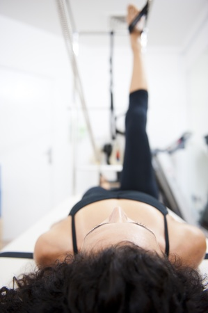 An attractive young lady performing a Pilates exercise with resistance from equipment.