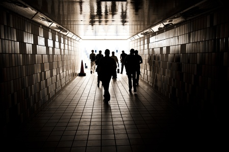Silhouettes of random unrecognizable people walking in a tunnel. Stock Photo