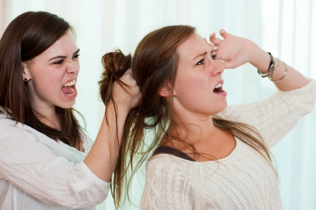 family fight: Sisters having an argument and getting physical with a fight  Stock Photo