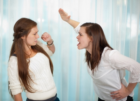 mean: Sisters having an argument and getting physical with a fight  Stock Photo